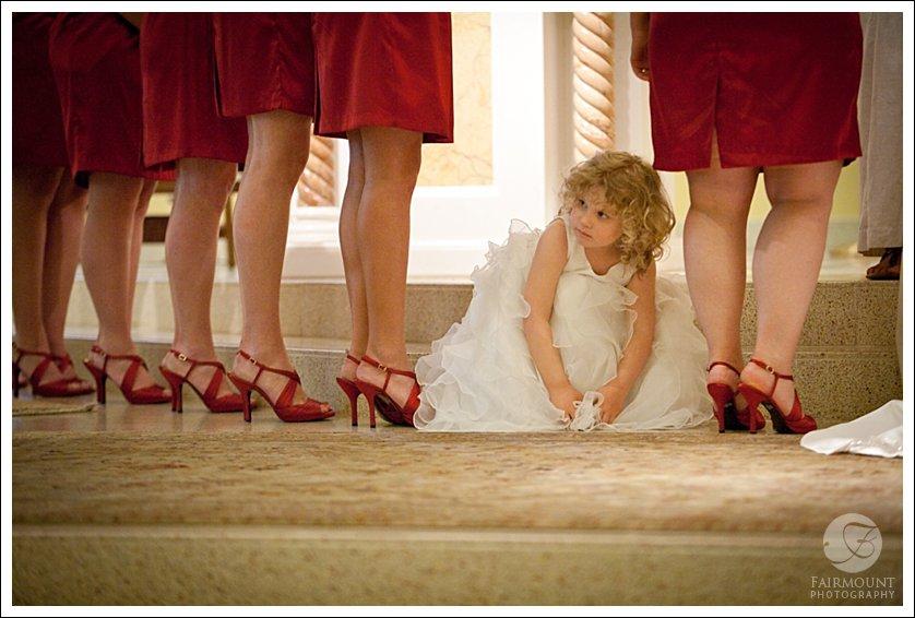 flower girl peeks out between legs of bridesmaids