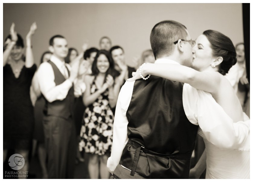 everyone cheers as bride and groom kiss at their wedding reception