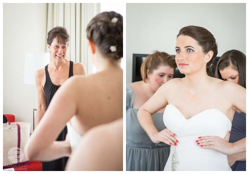 mother of the bride watches as bride puts on wedding dress