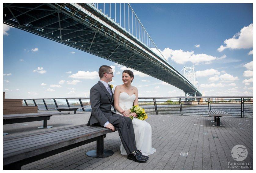 Bride & groom under the Ben Franklin Bridge at Race Street Pier