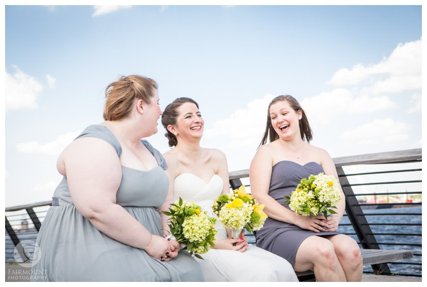 bride and bridesmaid laughing and having fun at Race Street Pier