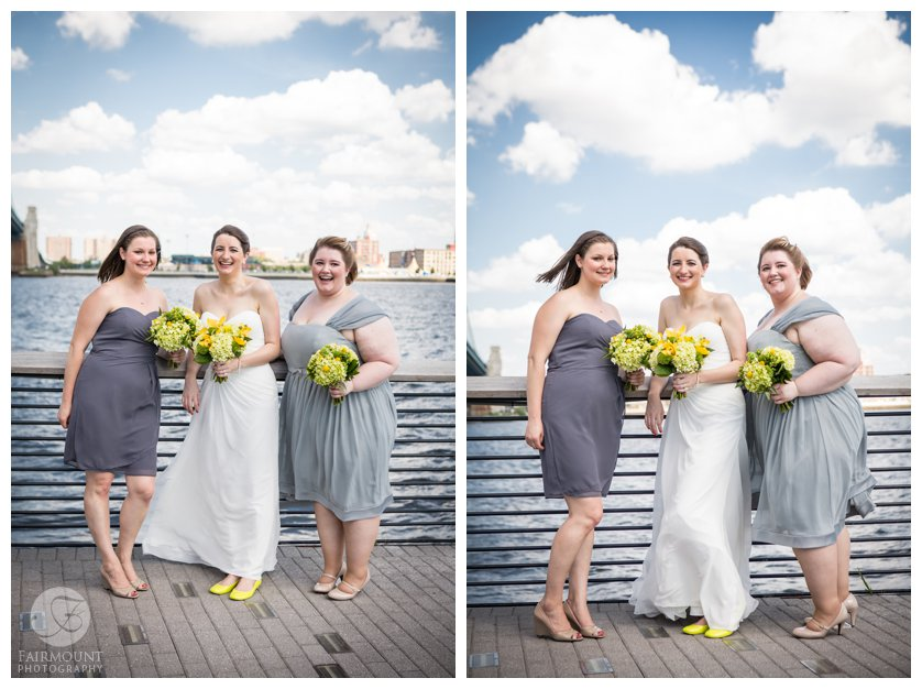 bridesmaids in grey dresses with yellow bouquets by the Delaware River