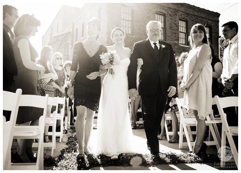 black & white portrait of bride walking down the aisle