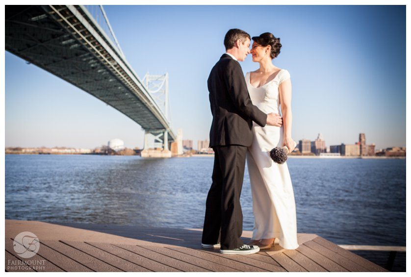 The Ben Franklin bridge stretches out behind Bride & Groom