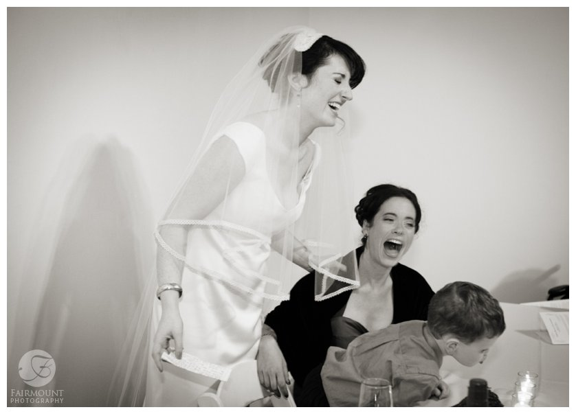 bride laughs with sister during the Tish, a Jewish pre-ceremony ritual