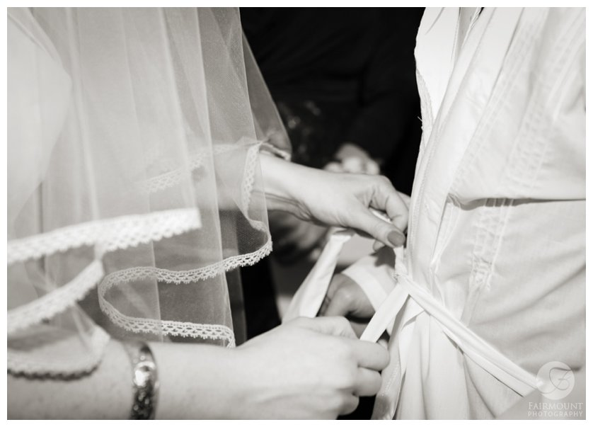 bride ties the belt of the kittel, a robe of white linen worn by the groom during the wedding ceremony