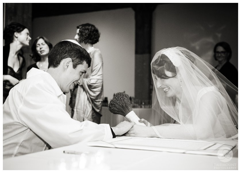 bride & groom smile at each other during the signing of the ketubah marriage contract