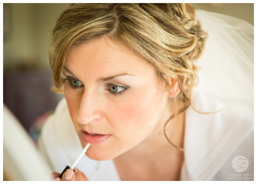bride applies lip glass for april wedding in PA
