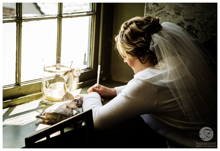 bride writes her vows while sitting in the window of a colonial home