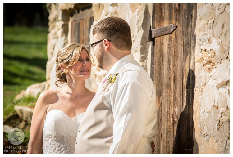 bride and groom in front of stone farmhouse