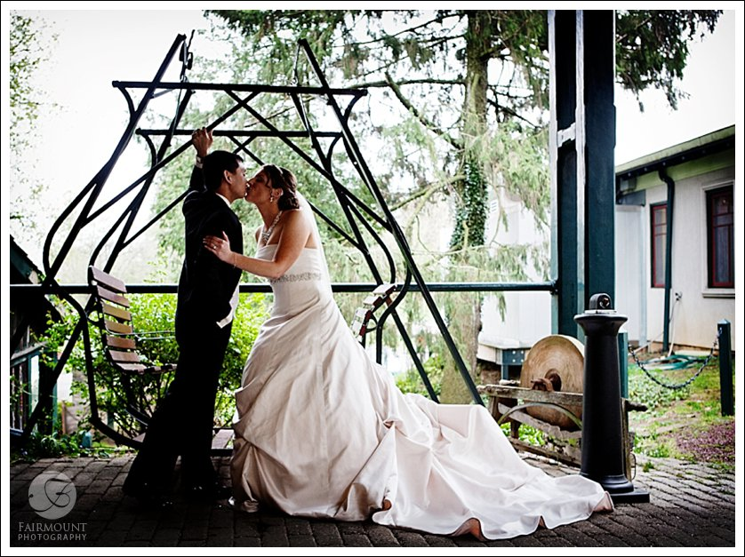Bride and Groom kiss in front of old two seat swing