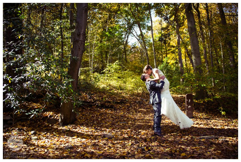 Groom lifts bride for kiss in woods in Fairmount Park