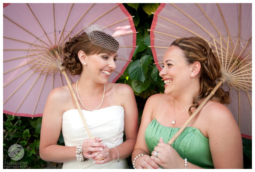 bride and maid of honor hold coral-colored paper parasols