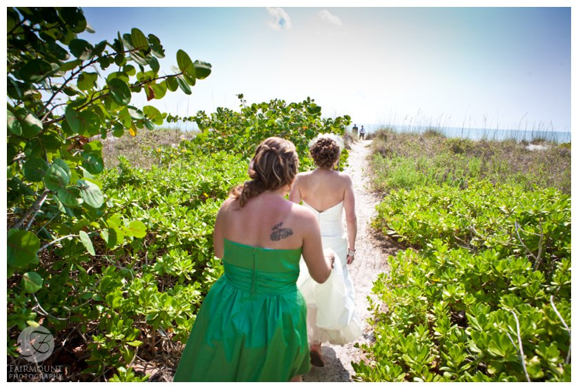 bride and maid of honor follow a path to the beach for first look at Sanibel Island destination wedding