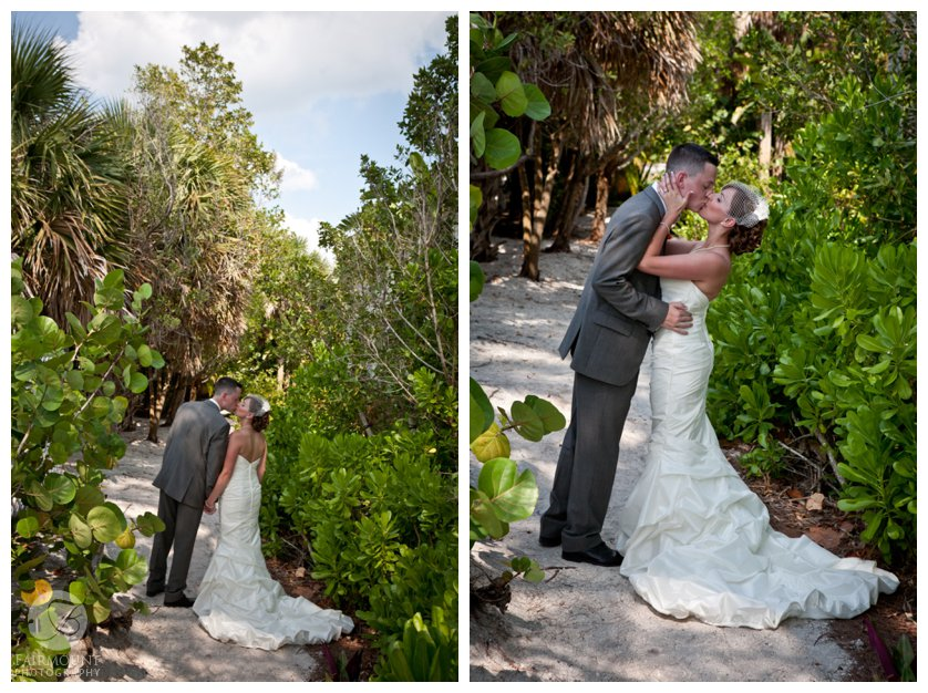 bride and groom kiss on sandy path through green vegetation at florida wedding