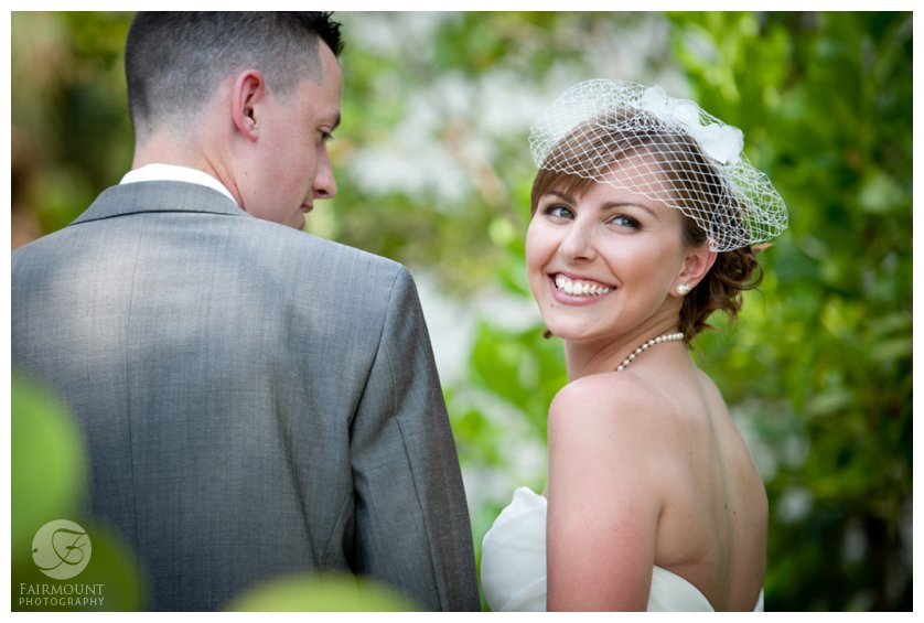 bride in a birdcage veil smiles after first look in Sanibel Island, Florida