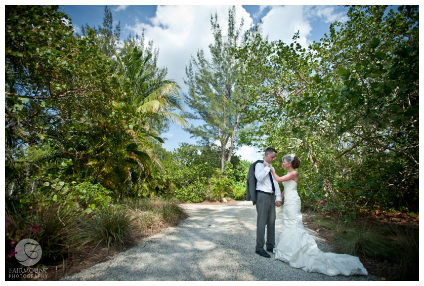Groom in gray suit and bride in mermaid gown for beach wedding in Sanibel Island, FL