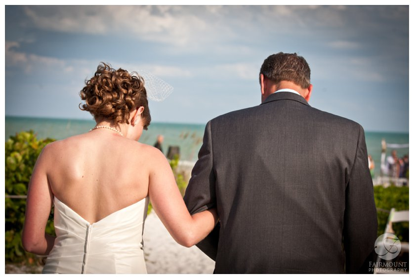 bride and her father walk down beach path to destination wedding in South Florida