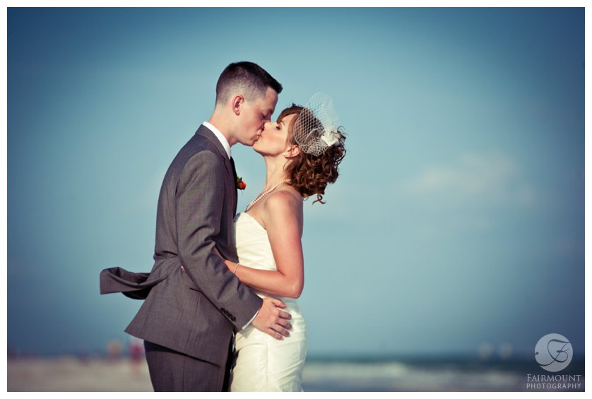 vintage-styled portrait of bride in birdcage veil and strapless dress kissing groom in gray suit on the beach