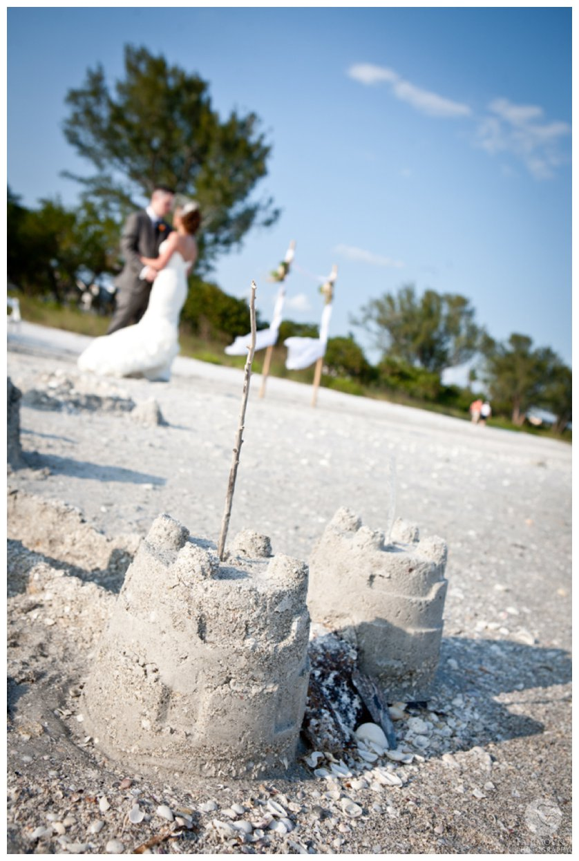 sandcastles on the beach with bride & groom in the background