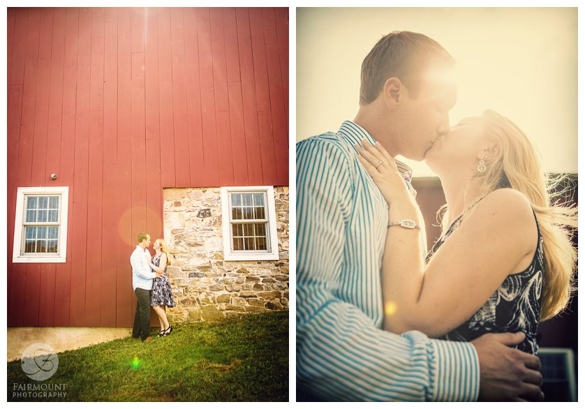 Engagement portrait outside red barn with lots of sun glare