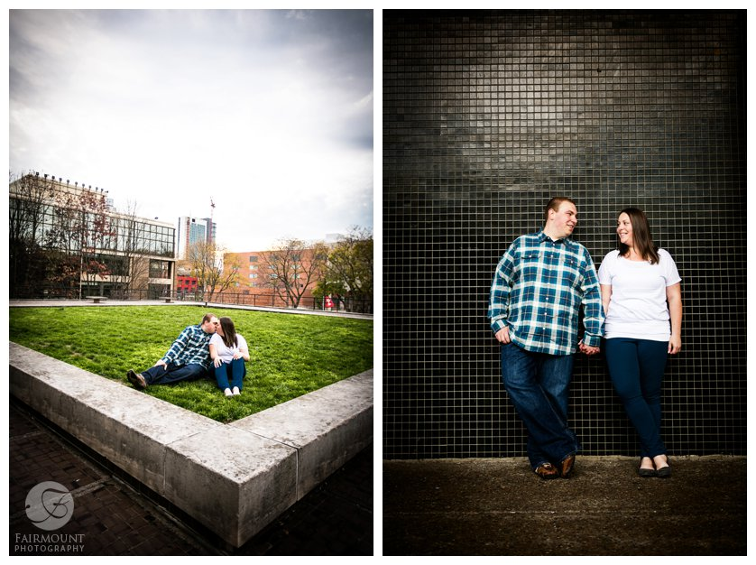 couple leans against black tile wall and kisses with Philadelphia in background