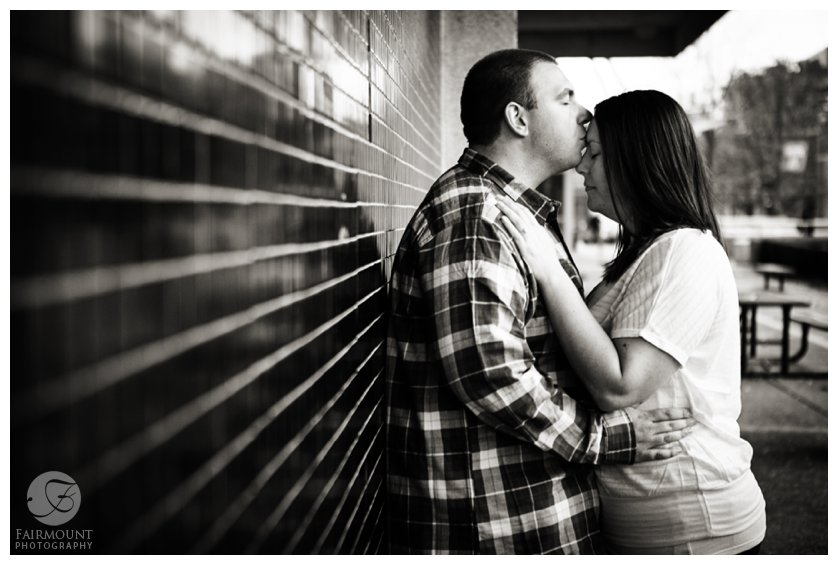 romantic portrait against black tile wall with guy kissing girl's forehead