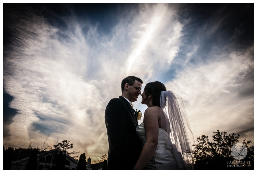 Bride and groom silhouette with cloudy sky