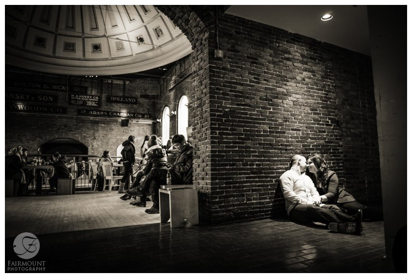 Couple cuddles inside Quincy Market during winter engagement session