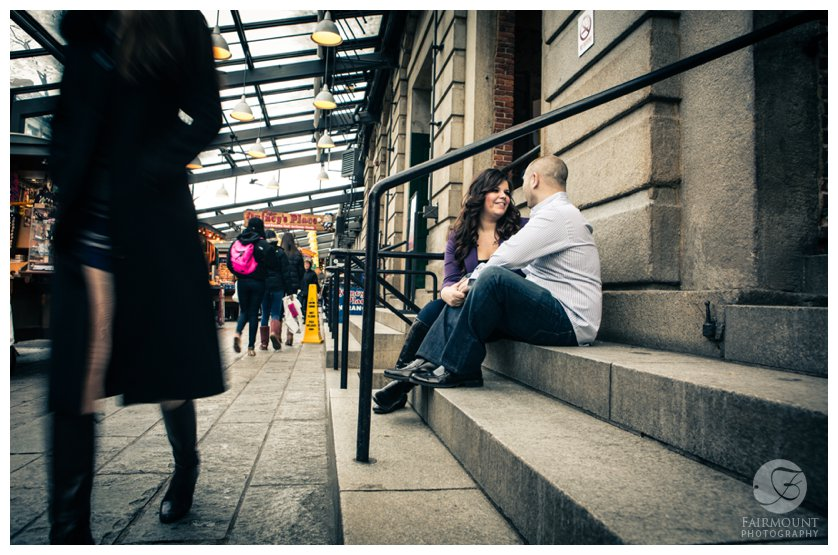 Couple sits on steps at Quincy Market shops