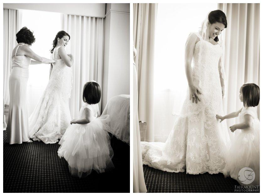 flower girl watches bride put on wedding gown