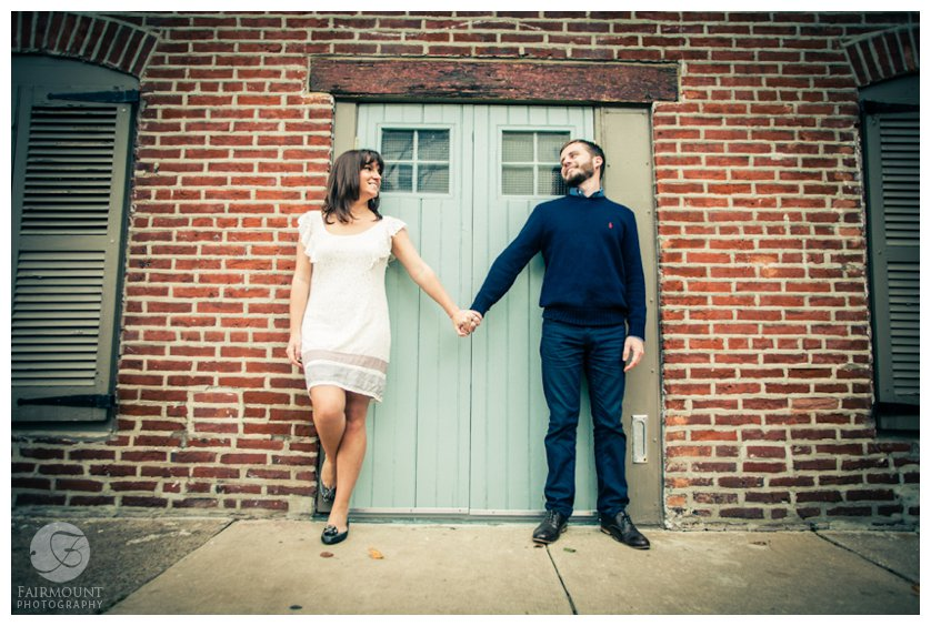 couple holds hands in front of tiffany blue door in brick wall in Philly