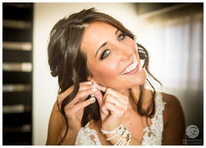 bride puts on earrings for Philadelphia wedding