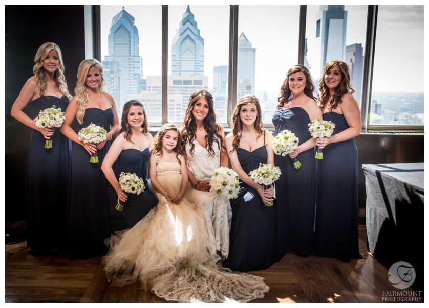 bride & bridesmaids on top floor of Loews hotel with Philadelphia skyline behind them