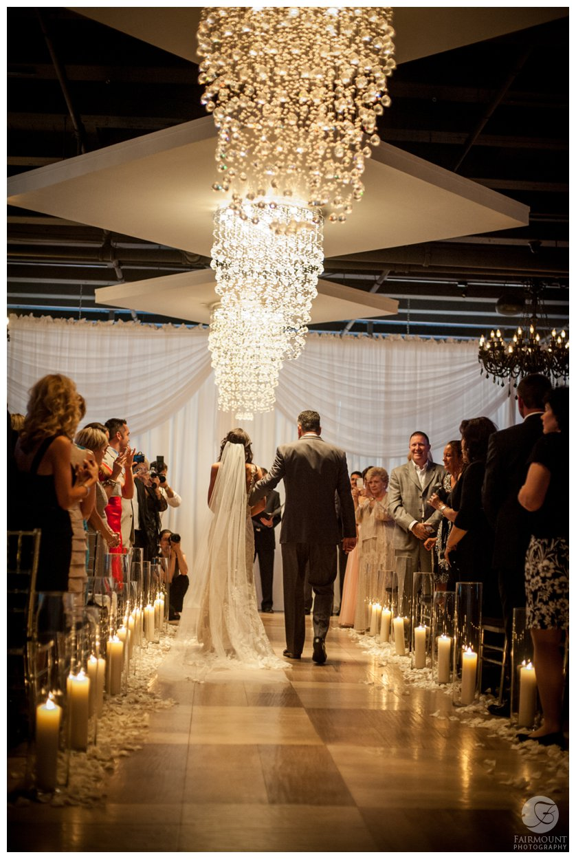 wedding ceremony at Tendenza with crystal chandeliers above the aisle