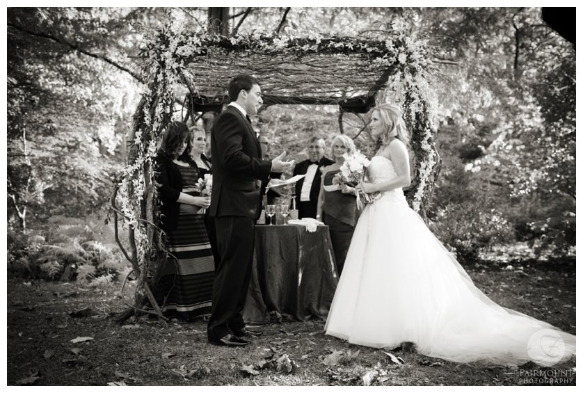 exchanging vows under chuppah made of branches