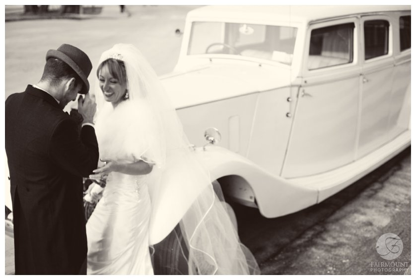 groom in fedora tips hat to bride leaning on antique car