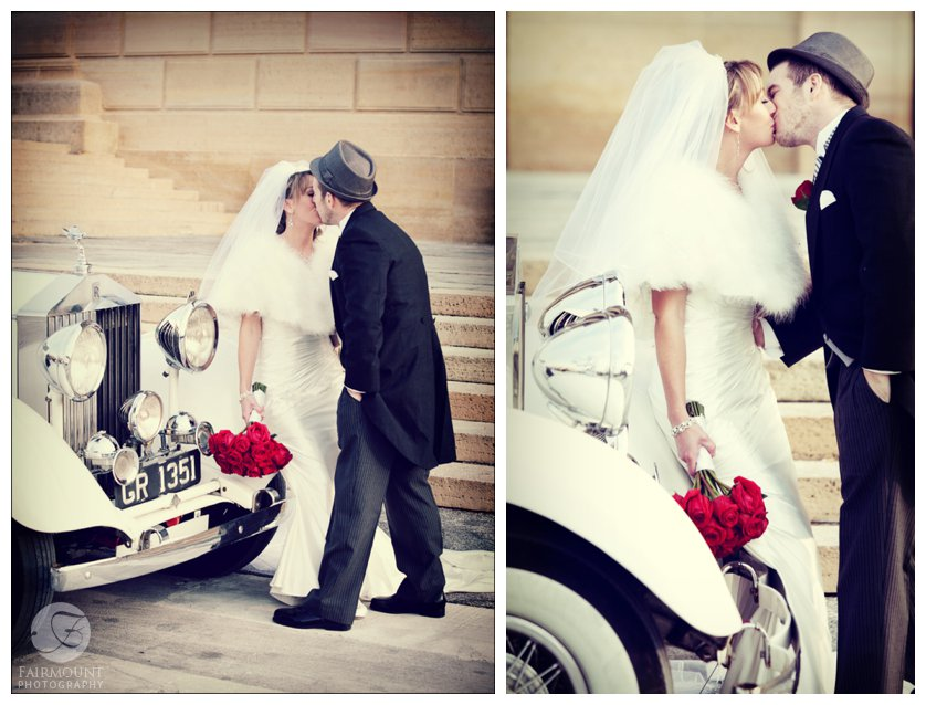 Groom in fedora and tails kisses bride with fur stole and red roses near antique car in Philadelphia, PA