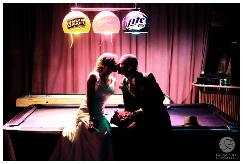 dramatic portrait of bride & groom sitting on a pool table at the Electric Factory