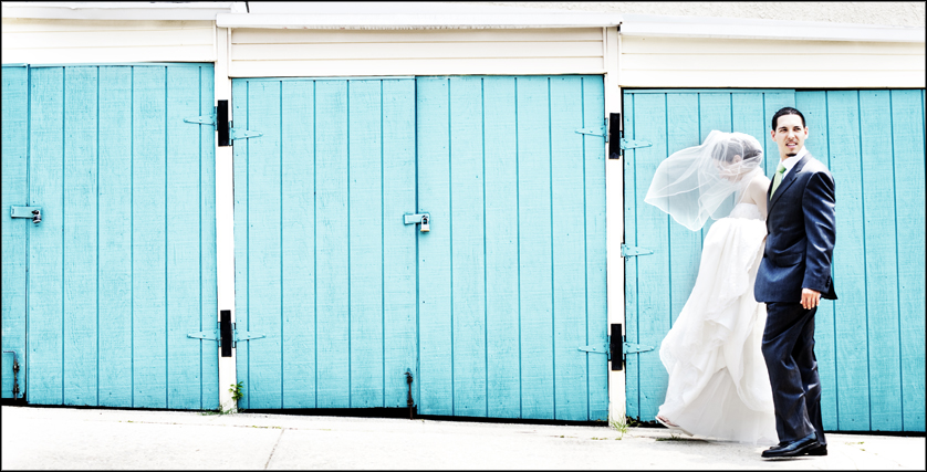 wind blows bride's veil with blue wall