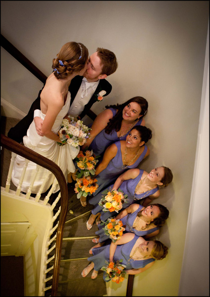 Photograph of the bridal party looking up at the bride and groom kissing at the Presbyterian Church of Chestnut Hill