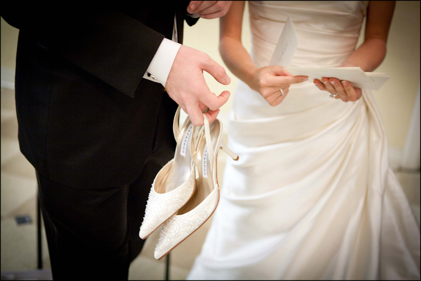 groom holds white shoes and bride holds cards