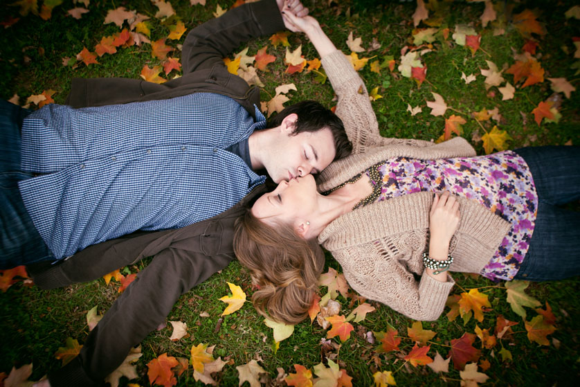 Engagement portrait of couple laying in grass with fall leaves around them