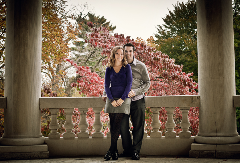 Smiling couple stands between columns outside historic Philadelphia mansion