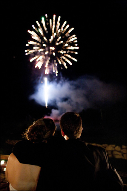 Happy couple watches fireworks light-up the night time sky