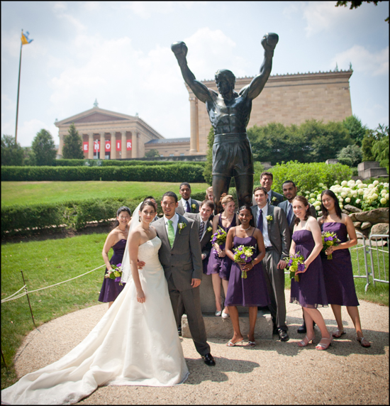 bridal party pose for photos in front of Rocky statue in Philadelphia