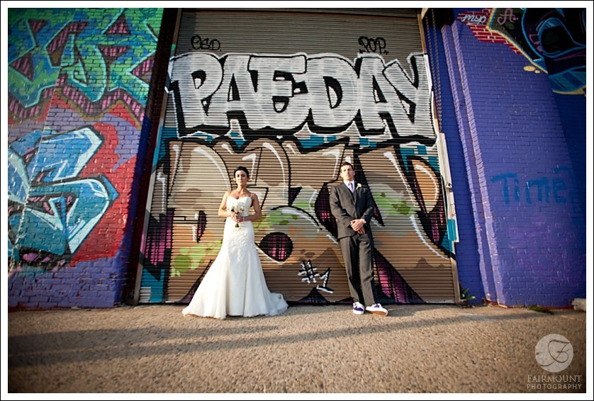 bride and groom by graffiti wall in North Philadelphia
