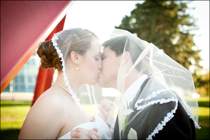 A bride's veil drapes over her groom's head too as they kiss at Muhlenberg College