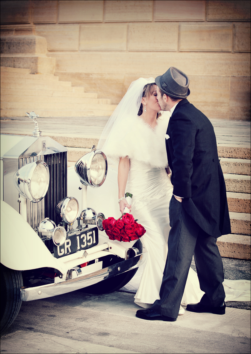 A Bride and Groom kiss next to a vintage car in front of the Philadelphia Museum of Art.