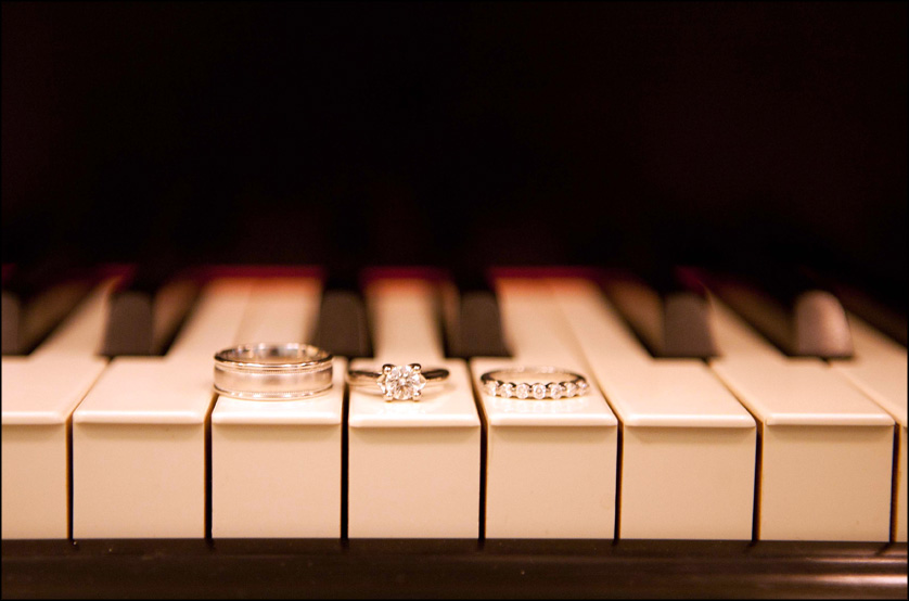 Wedding rings are photographed on the keys of a piano